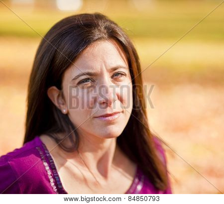 Sad beautiful woman outdoors against fall leaf background