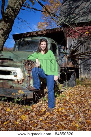 Pretty woman leaning on an abandoned old truck in the fall