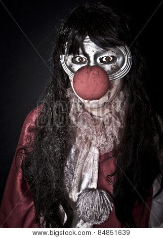 Unidentifiable woman in halloween clown costume with painted eyes