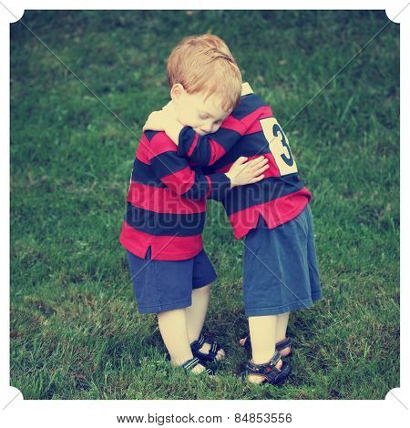 Twin baby boys hugging in rugby clothing with Instagram effect filter