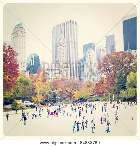 Ice skaters having fun in New York Central Park in fall with Instagram effect filter