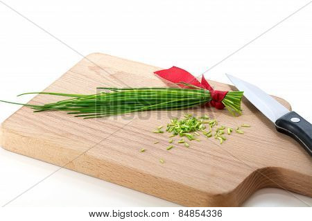 Bunch Of Chives And Kitchen Knife On A Cutting Board