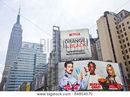 NEW YORK, USA - JUNE 28th 2014: The iconic Empire State Building and popular TV show Orange is the new Black billboard poster.