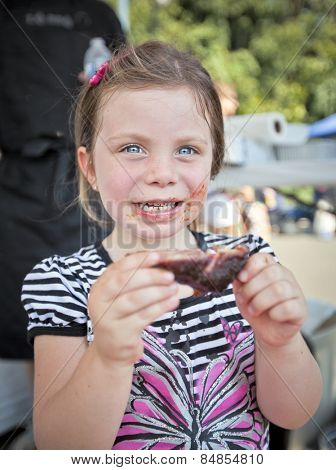 Young girl chewing on a BBQ pork rib