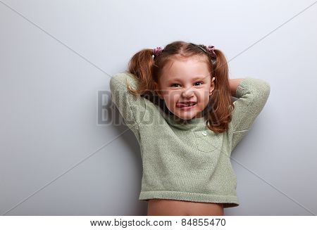 Happy Smiling Girl Looking And Showing Tongue On Blue Background