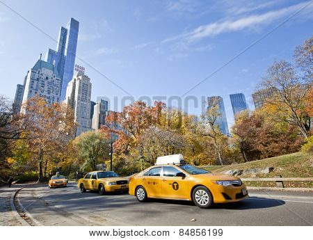 NEW YORK, USA - NOVEMBER 13th, 2014: Yellow taxi cabs driving through Central Park with skyscraper background in the fall
