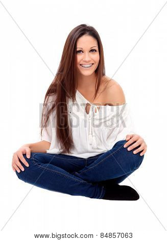 Casual young girl with brackets sitting isolated on a white background