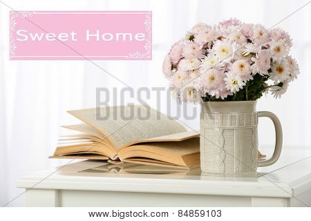 Beautiful flowers in cup on window background and space for your text