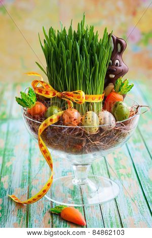 Easter composition with fresh green grass,eggs and chocolate bunny