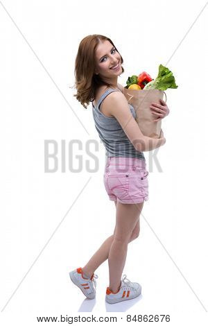 Back view portrait of a smiling woman holding a shopping bag full of groceries