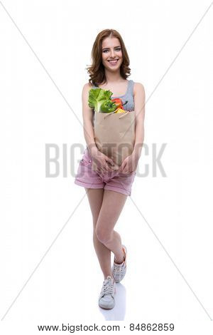 Full length portrait of a happy woman holding a shopping bag full of groceries