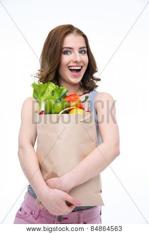 Laughing woman holding a shopping bag full of groceries
