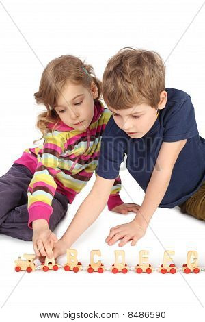 Little Boy And Girl Playing With Wooden Railway Sitting On Floor Isolated On White