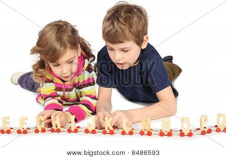 Little Boy And Girl Playing With Wooden Railway, Lying On Floor, Full Body, Isolated On White