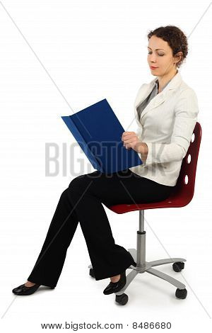 Young Attractive Woman In Business Dress Sitting On Chair And Reading A Book, Side View, Isolated