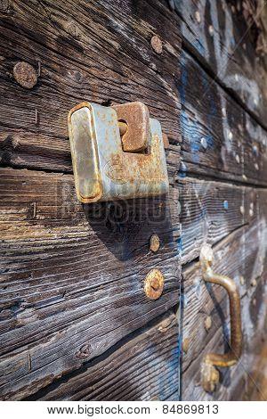 Rusty padlock and wooden door