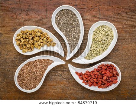 superfood samples  (mulberry, chia seeds, hemp seeds, goji berry, flax seed) in teardrop shaped bowls against grunge wood