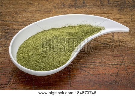 organic wheatgrass powder on a white teardrop shaped bowl against rustic wood