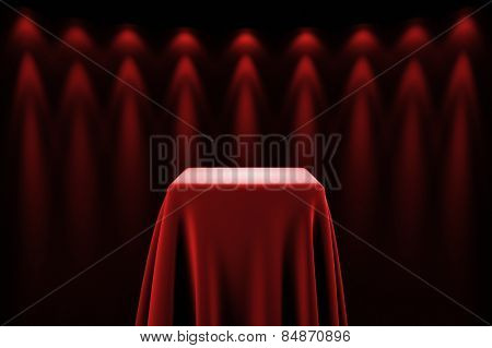 Presentation pedestal covered with a red silk cloth in front of a wall illuminated by spot lights