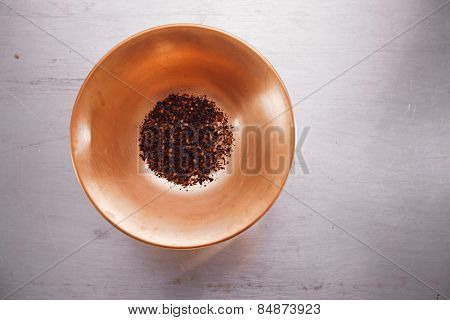 chipotle - jalapeno smoked whole chili  in copper bowl on  textured tin metal backdrop