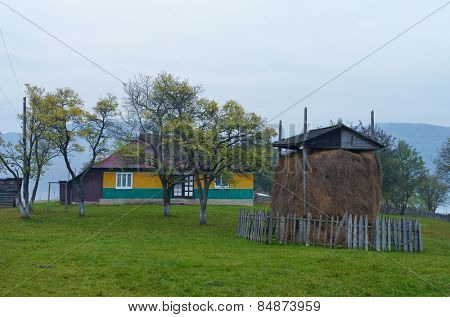 Haystack on the lawn. Yard in a mountain village. Wooden house. Carpathians, Ukraine, Europe