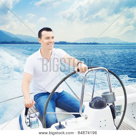 A young and handsome Caucasian man sailing in the sea on a boat on a sunny day.