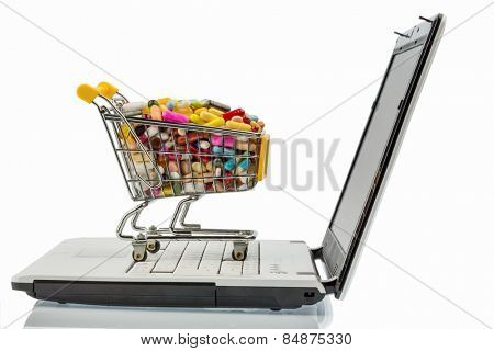 tablets with shopping cart and computer. photo icon for the purchase of drugs on the internet