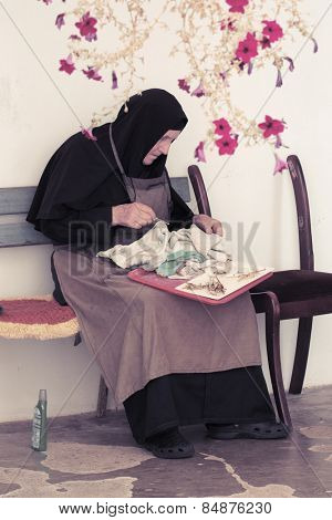 FRUSKA GORA, SERBIA - AUGUST 04 2014: an elder nun is polishing the brass. in the courtyard of Grgeteg Monastery on Fruska Gora mountain in the northern Serbia.