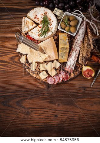 Cheese and salami arrangement served on cutting board. Shot from aerial view