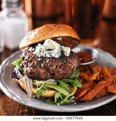 gourmet burger with blue cheese and sweet potato fries on metal plate.