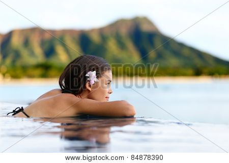 Infinity pool resort woman relaxing at sunset overlooking Waikiki beach in Honolulu city, Oahu island, Hawaii, USA. Wellness and relaxation concept for summer vacations.