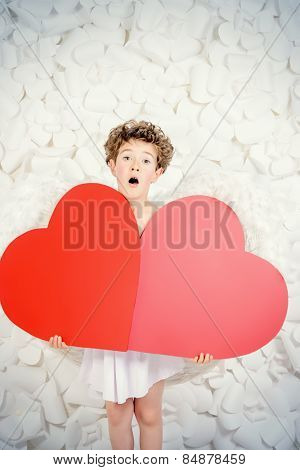 Portrait of a lovely emotional little boy in a costume of angel holding red hearts. Cupid. Valentine's day.