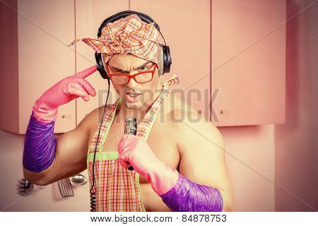 Funny and handsome muscular man in an apron and headphones singing into a microphone in the pink kitchen. Love concept. Valentine's day. Women's day.