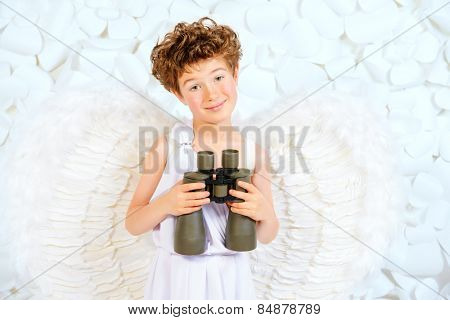 Cute little boy in a costume of angel looking through the binoculars. Cupid. Valentine's day.