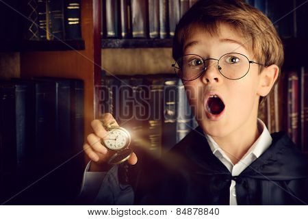 Surprised boy stands with watch in the library with many old books. Fairy tales. Vintage style.