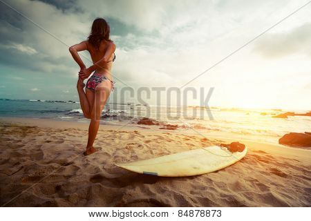 Young lady stretching on the beach before surfing