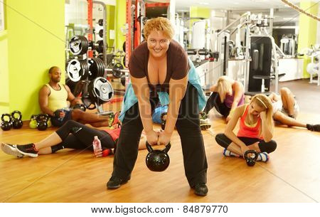 Determined fat woman doing fitness workout in gym, all the others exhausted.
