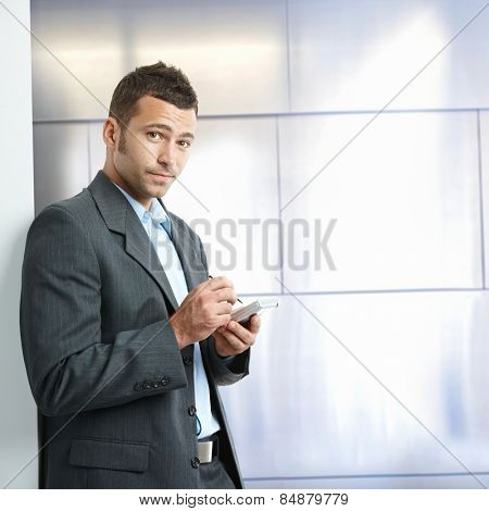 Annoyed young caucasian businessman in suit with tablet, standing in front of wall at business office. Looking at camera, copyspace.