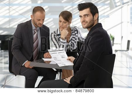 Caucasian businessman on meeting reading business report, looking back over the shoulder, smiling.