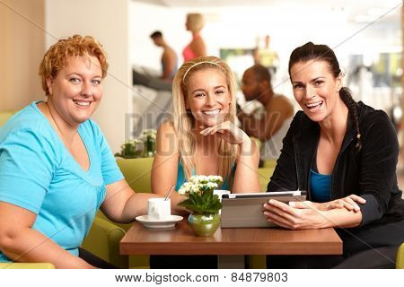 Happy female companionship sitting around table in gym coffee, resting, talking, looking at photos, smiling, looking at camera.