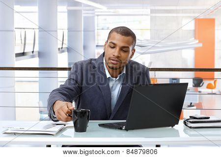 Casual black businessman working with laptop computer at office desk.