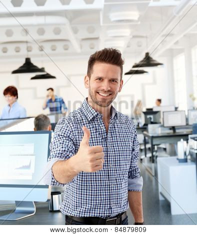 Happy casual man showing thumb-up in office, smiling.