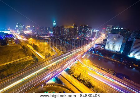 traffic light trails on overpass and cityscape at night