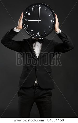 Handsome young man wearing a tuxedo and holding a clock
