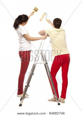 Loving couple painting the wall in the apartment. Isolated on white background