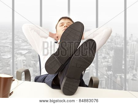 Businessman sleeping. Businessman reclining with his feet up on desk in office