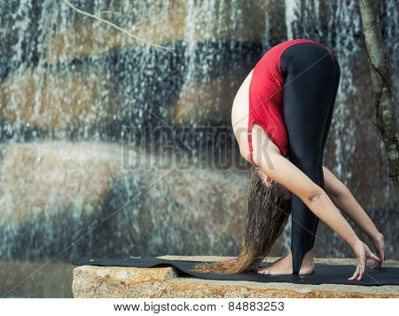 Woman practicing yoga near waterfall. Standing Forward Bend. Uttanasana