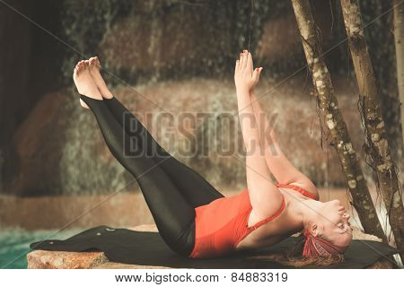 Young woman is practicing yoga near waterfall. Toned