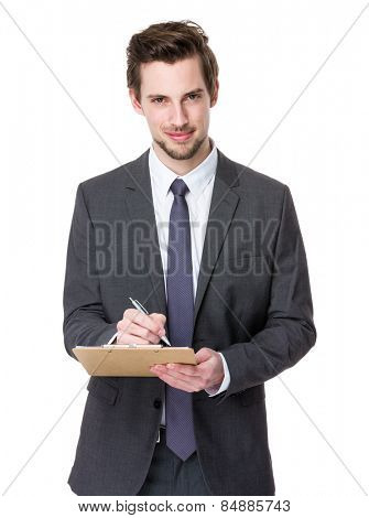 Caucasian businessman write on clipboard