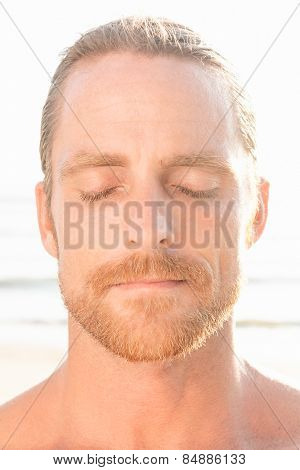 Quiet meditative handsome man with a beard standing at the beach in the tropical sunshine with his eyes closed in peace and tranquility